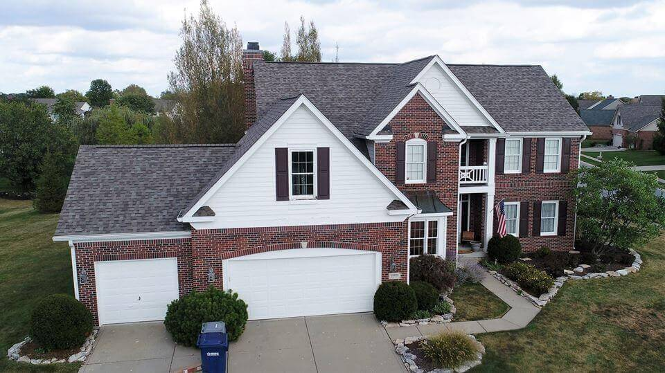 brick and white home with dark gray roof